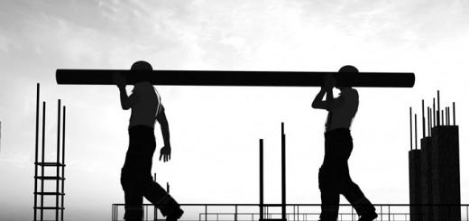 Mehrere Bauarbeiter errichten ein Stahlgerüst