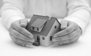 Hausmodell wird von schützenden Händen umgeben