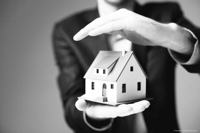 Mann hält Miniaturhaus zwischen den Händen