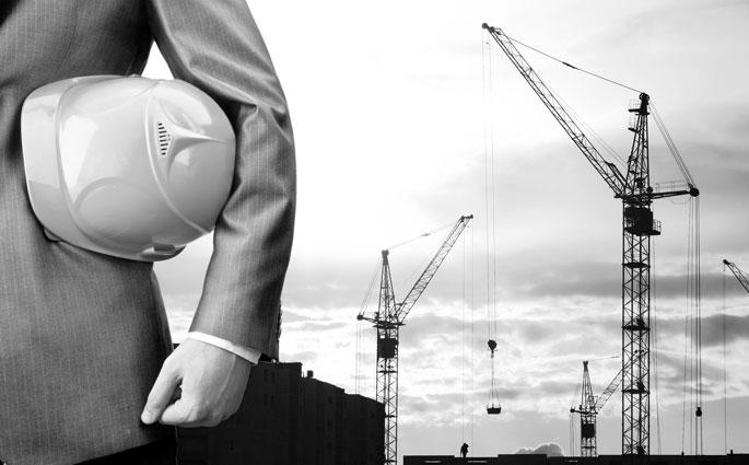 Mann mit Anzug und Helm auf der Baustelle